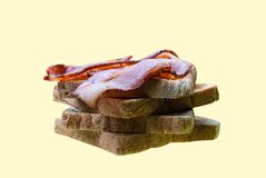 Grilled wholewheat bread and bacon on top of it as a breakfast s. Andwiches isolated on cream color background, day starting Royalty Free Stock Photography