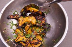 Grilled winter squash salad in a stainless steel bowl with serving spoon Stock Photo