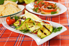 Grilled zucchini. Served on a plate with lemon and tomato Stock Image