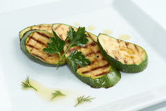 Grilled zucchini decorated with green leaf on white plate Stock Photo