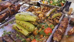 Grilled zucchini, mushroom with parsley. Heaps of grilled food on background. Barbecue vegetables at the street food. Grilled zucchini, mushroom with parsley stock video footage