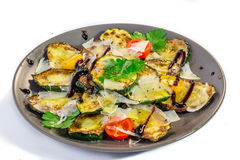 Grilled zucchini with olive oil, parmesan and balsamico. Isolated on white stock photography