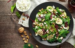 Grilled Zucchini salad with feta cheese, walnut nuts and glass of red wine in a black plate on wooden table.  royalty free stock photo