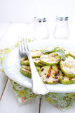 Grilled zucchini in a white plate with a fork. Decorated with basil stock photos