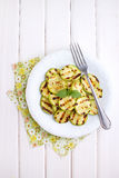Grilled zucchini in a white plate with a fork. Decorated with basil royalty free stock photo