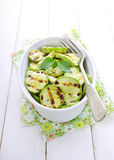 Grilled zucchini in a white plate with a fork. Decorated with basil royalty free stock image
