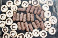 Grillen des Fleisches mit Pilzen Lizenzfreie Stockbilder