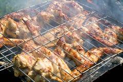 Grillen des Huhns auf einem Grill im Rauche Stockfotografie