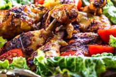 grillen Gegrilltes Huhn Gegrillte Hühnerbeine Gegrillte Hühnerbeine, Kopfsalat und Kirschtomaten Traditionelle Küche Mediterra Lizenzfreies Stockfoto
