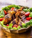 grillen Gegrilltes Huhn Gegrillte Hühnerbeine Gegrillte Hühnerbeine, Kopfsalat und Kirschtomaten Traditionelle Küche Mediterra Lizenzfreie Stockbilder