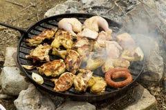 Grillen Sie über geöffnetem Feuer mit Fleisch und Huhn Stockfoto