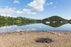 Grillen Sie Asche durch schönen See auf ruhigem idyllischem Sommermorgen mit Wolkenreflexionen Lizenzfreies Stockfoto