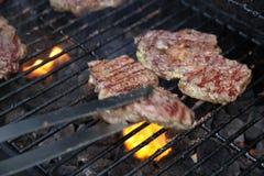 Grillen Sie Fleisch auf Grill mit Greifern in der Bewegung Stockbild