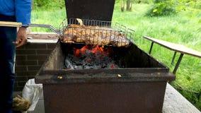 Grillen Sie Grill Nahaufnahme Manchmal dreht ein Mann das Fleisch auf dem Grill Das Konzept der köstlichen Nahrung und Erholung d stock footage