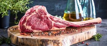 Grillen Sie Kriegsbeil-Steak auf dunklem Hintergrund mit dem Kraut, das für Grill zugebereitet wird stockfotografie