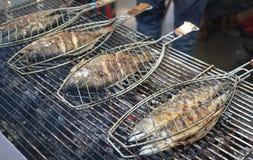 Grillen von Fischen auf einem Grill lizenzfreie stockfotos