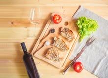 Grillen von Schweinefleischsteaks auf Schneidebrett, Flasche Rotwein, leeren Weinglas-, Gabel- und Salatblättern lizenzfreies stockbild