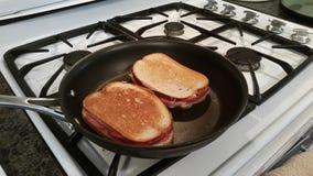 Griller des sandwichs à fromage et à viande Image libre de droits