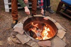 Griller des saucisses au-dessus d'un feu de camp, campeurs rôtissant des saucisses sur des fourchettes de grillage L'endroit du f Image libre de droits