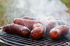 Griller des saucisses sur le gril de barbecue Images libres de droits