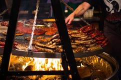 Griller le bifteck et les saucisses Photographie stock