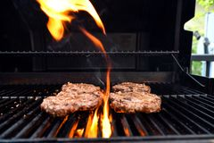 Griller les hamburgers faits maison sur un barbecue avec des flammes image libre de droits