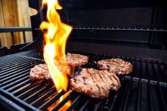 Griller les hamburgers faits maison sur un barbecue avec des flammes image stock
