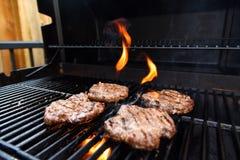 Griller les hamburgers faits maison sur un barbecue avec des flammes photos libres de droits