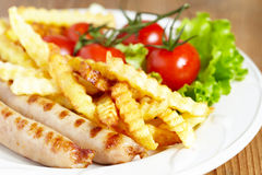 Grilles sausages with french fries and salad Royalty Free Stock Photo