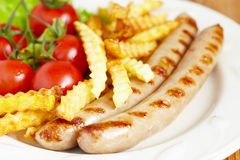 Grilles sausages with french fries and salad Stock Images