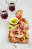 Grillez avec du jambon, des olives et des tomates-cerises dans le conseil olive Photo stock