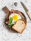 Grillez avec l'oeuf au plat, le lard et l'arugula sur la planche à découper en bois Petit déjeuner délicieux sur un fond clair Images stock