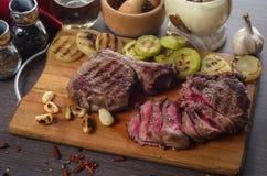 Grillez la composition en bifteck d'oeil de nervure de viande sur le fond en bois Images stock