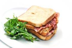 Grillez le sandwich avec du jambon, le fromage, l'oignon et la salade du plat blanc, sur le fond blanc Photos libres de droits