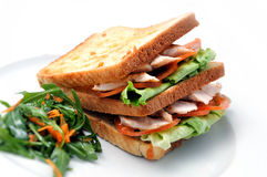 Grillez le sandwich avec le poulet, les tomates, la laitue et la salade du plat blanc, sur le fond blanc Images libres de droits