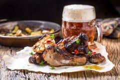Grillez les nervures rôties juteuses de porc de nervures de porc avec la bière pression sur la table de chêne rustique Photographie stock libre de droits