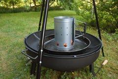 Grillez tout entier le démarreur de cheminée de charbon de bois sur un gril noir de pivot de trépied image libre de droits