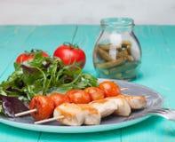 Grillez tout entier le poulet avec des tomates dans un plat avec de la salade Image stock