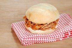 Grillez tout entier le sandwich tiré à porc sur le somme rouge et blanc Photographie stock libre de droits