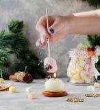 Grillez une guimauve au-dessus d'une bougie pendant Noël et la nouvelle année sur une table blanche en bois, foyer sélectif Photos libres de droits