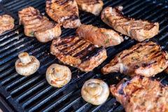Grillfestgaller kopplar av in tid av familjpartiet som lagar mat kött, champinjoner och grillfestgallret för familj Grillat kött  Royaltyfria Foton