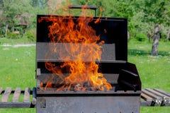 Grillgrill mit Feuer im Abschluss des Gartens im Freien herauf Ansicht stockfotografie