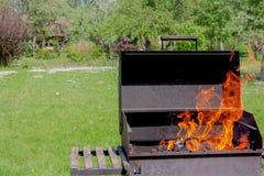 Grillgrill mit Feuer im Abschluss des Gartens im Freien herauf Ansicht lizenzfreie stockfotografie