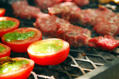 Grilling. A grilling meat and tomatoes Royalty Free Stock Images