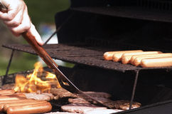 Grilling. Hotdogs and hamburgers on the grill at a summer cookout Stock Images