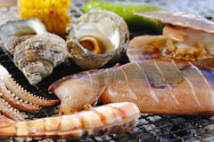 Grilling abalone, squid, shrimp, clams and corn with hot charcoa. L deliciously Royalty Free Stock Photos
