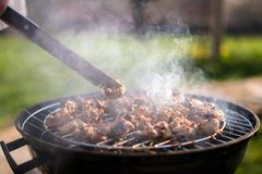 Grilling barbeque meet on the grill outdoors in the back yard. Summer time picnic. Roasting meat on metal grid on hot coals. Smoke royalty free stock image