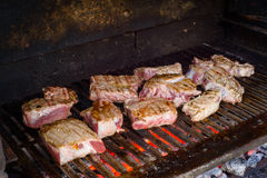 Grilling beef meat. Many piece of beef meat grilling on a barbecue Royalty Free Stock Photo
