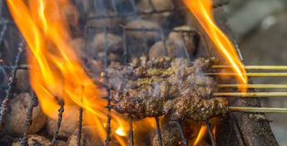 Grilling Beef Satay. Beef satay on the barbecue grill Royalty Free Stock Images