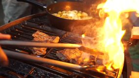 Grilling Beef Steak on flaming griller stock video footage
